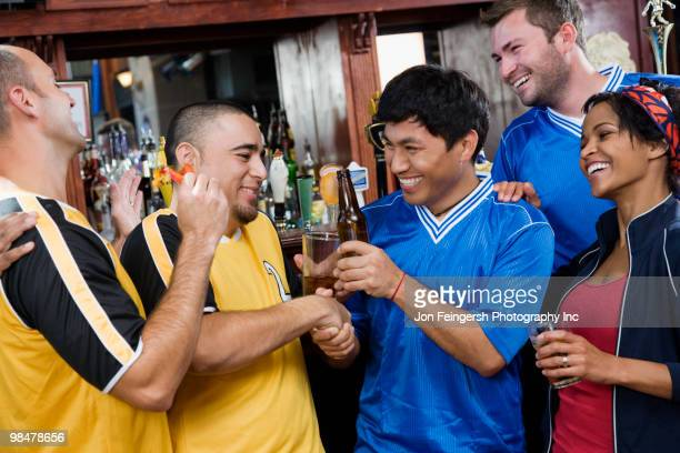 happy men shaking hands in sports bar - rivaliteit stockfoto's en -beelden