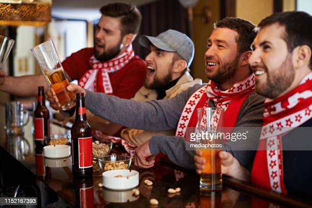 hommes heureux regardant le jeu de sport dans le pub - club football photos et images de collection