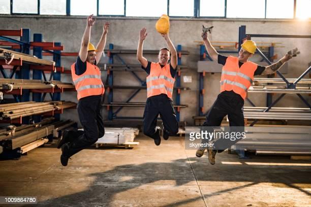 Glücklich Metallarbeiter Spaß beim springen in Aluminium-Mühle.