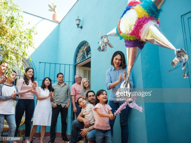 happy mexican girl hitting piñata with stick and family looking - tradition stock pictures, royalty-free photos & images