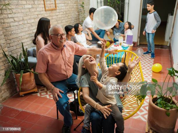 happy mexican grandparents and grandson playing with balloon - tradition stock pictures, royalty-free photos & images