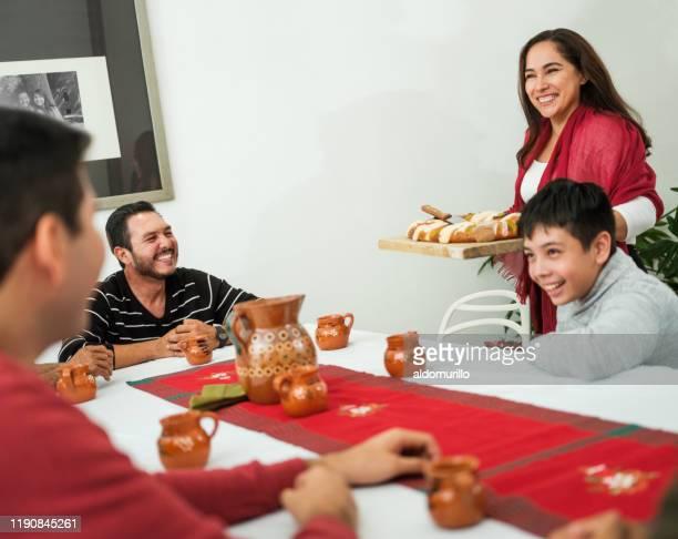 feliz mujer mexicana trayendo pan tradicional en la mesa - rosca de reyes fotografías e imágenes de stock