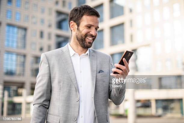 happy mid adult businessman checking email. - convenience stock pictures, royalty-free photos & images