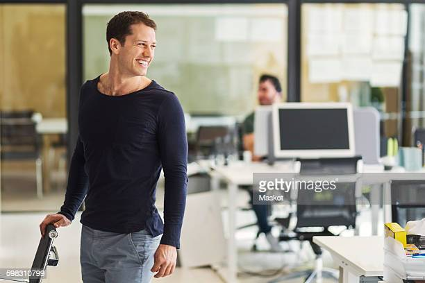 Happy mid adult businessman looking away with colleague in background at office