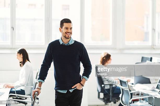 Happy mid adult businessman with colleagues working in background at office