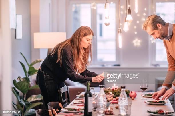 felice coppia media adulta che organizza tavolo da pranzo con decorazione natalizia - candela attrezzatura per illuminazione foto e immagini stock