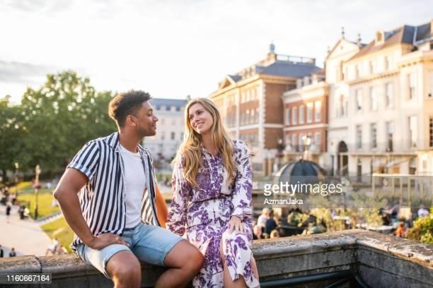 happy mid adult couple sitting on richmond bridge at sunset - river thames stock pictures, royalty-free photos & images