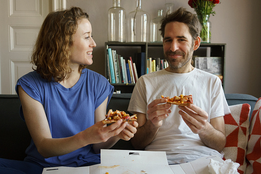 Happy mid adult couple sitting on sofa eating fresh pizza in living room at home - gettyimageskorea