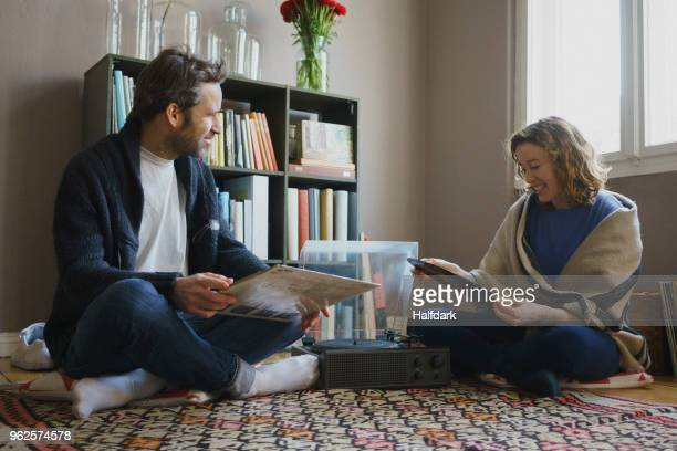 happy mid adult couple sitting with records by turntable on carpet at home - ricordi foto e immagini stock