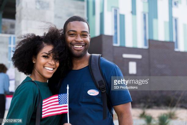 happy mid adult couple smiles for camera after voting - citizenship stock pictures, royalty-free photos & images