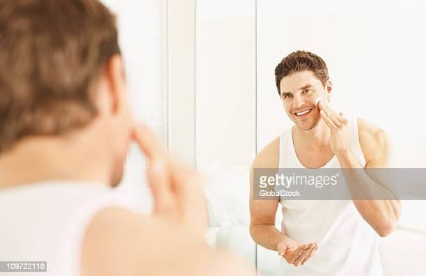Glücklich Mann mittleren Alters Anwendung der Creme auf Gesicht