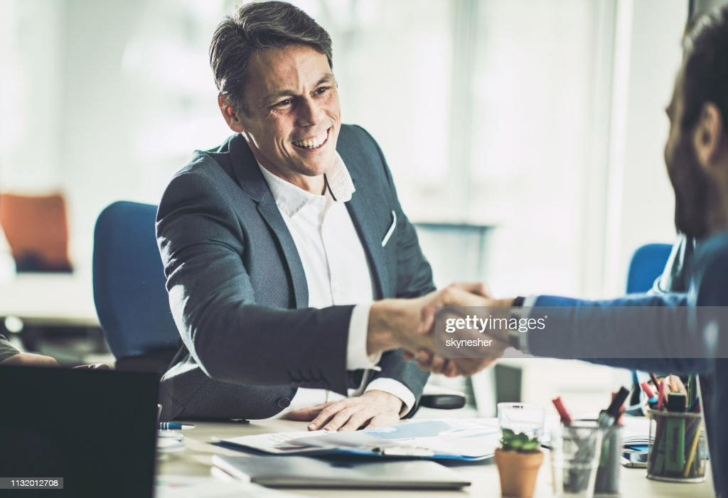 Happy mid adult insurance agent shaking hands with his customer in the office. : Stock Photo