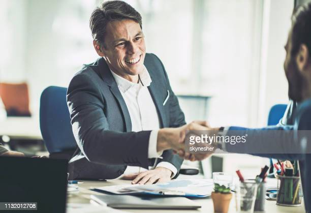 happy mid adult insurance agent shaking hands with his customer in the office. - advice stock pictures, royalty-free photos & images
