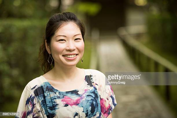 Happy mid adult Japanese woman smiling towards camera