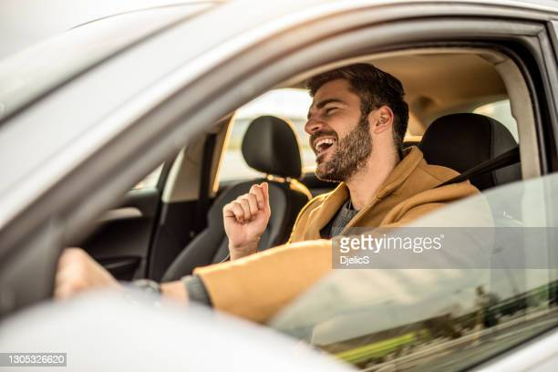 happy mid adult man driving a car and singing. - listening stock pictures, royalty-free photos & images