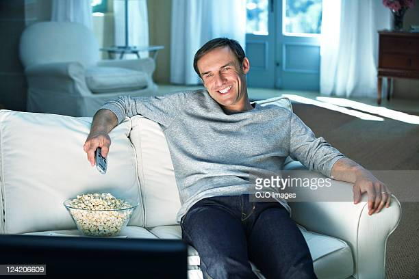happy mid adult man enjoying television with bowl of popcorn on couch - one man only stock pictures, royalty-free photos & images