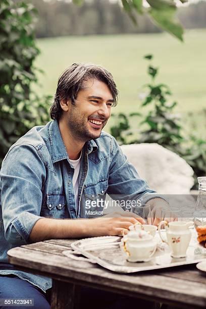 Happy mid adult man having breakfast at organic farm