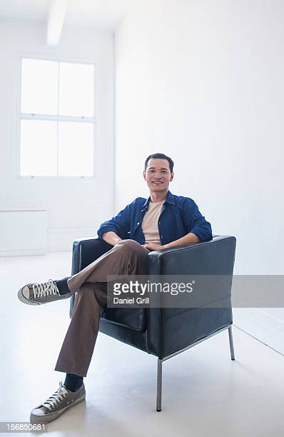 Happy mid adult man sitting in his armchair