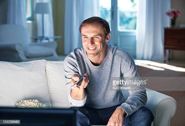 happy mid adult man sitting on sofa with a remote control - changing channels stock photos and pictures