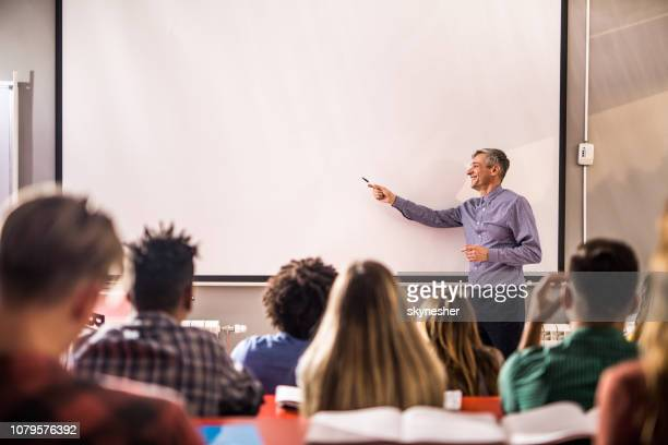 happy mid adult professor teaching a lecture on visual screen in the classroom. - lecturer stock pictures, royalty-free photos & images