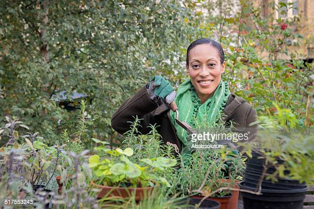 Happy Mid Adult Woman In Urban City Garden Potting Plants