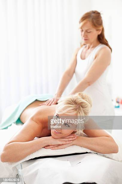 Happy mid adult woman looking away while lying on massage table with masseur in background