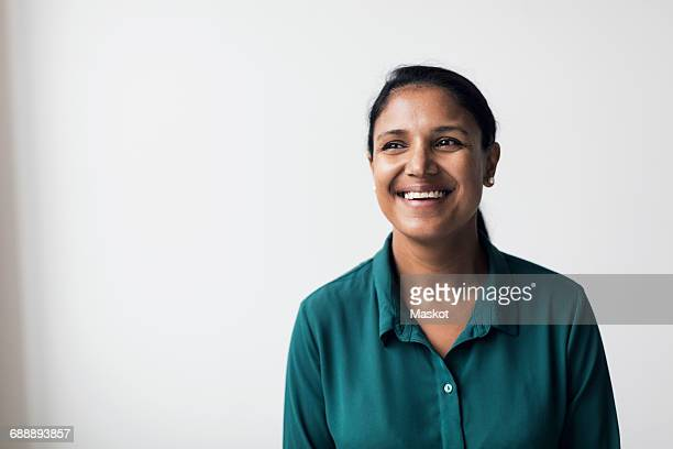 happy mid adult woman looking away while standing against white background - indian woman stock photos and pictures