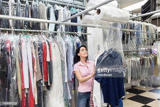 happy mid adult woman looking up while putting clothes in plastic - dry cleaner stock pictures, royalty-free photos & images