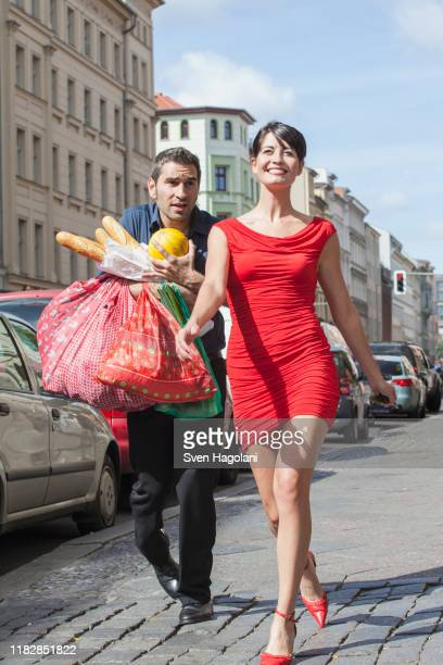 happy mid adult woman walking while man carrying groceries on street - beautiful dominant women stock pictures, royalty-free photos & images
