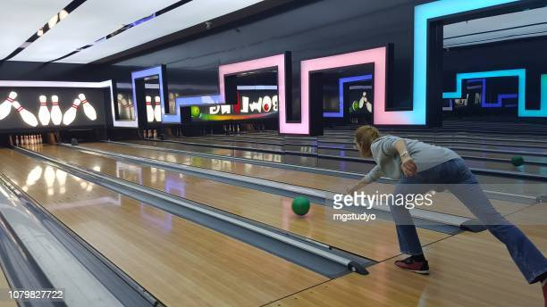 happy mid adult women playing bowling - bowling alley stock pictures, royalty-free photos & images
