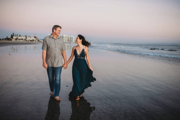 Happy mid-40's couple gazing at each other while walking on the beach