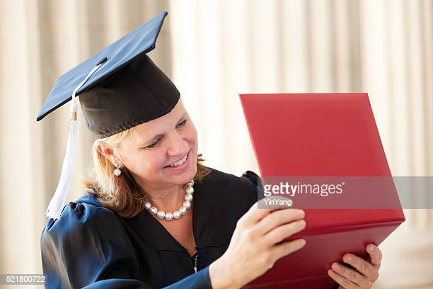 Happy Middle Age Woman Looking at Diploma in Graduation Horizontal