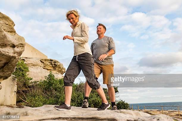 小さめのフィットな中心的な屋外のビーチのカップルのハイキング