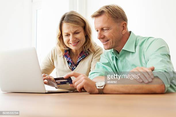 Happy middle aged couple doing online shopping