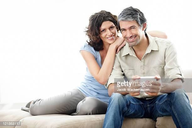 feliz pareja en sofá de medio - pareja hombre mayor y mujer joven fotografías e imágenes de stock