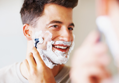 Happy middle aged man using razor to shave 109720549