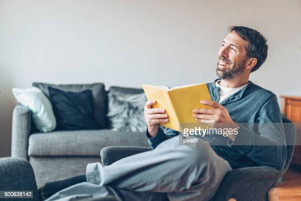 feliz meio velho com um livro em casa - lendo - fotografias e filmes do acervo