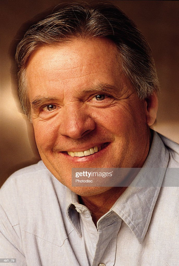 happy middle aged man with graying hair wearing a light gray shirt smiles : Stock Photo