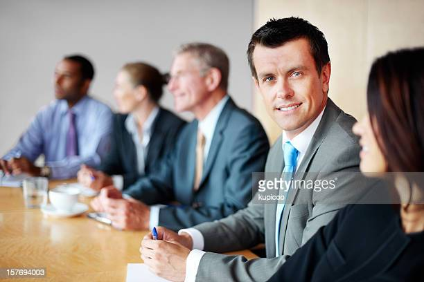 Happy middle aged man with his team in a meeting