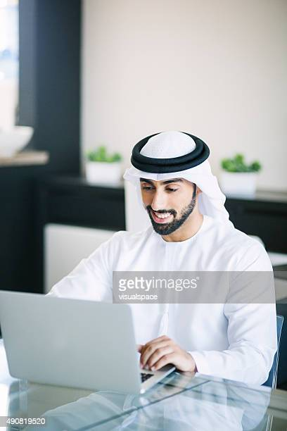 Happy Middle Eastern Man Using Laptop at Home