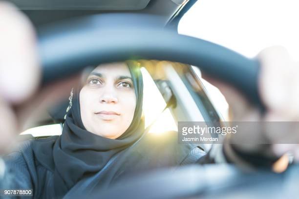 Happy Middle Eastern woman driving a car