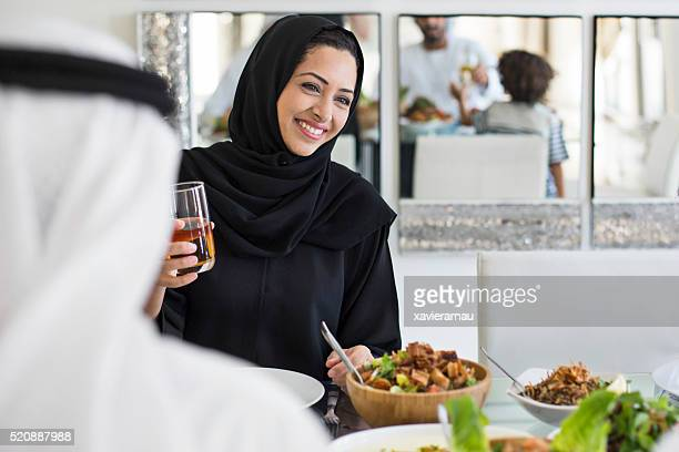 Happy Middle Eastern woman eating with family