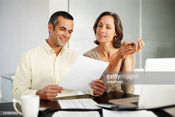 Happy, middle-aged couple working on financial expenses