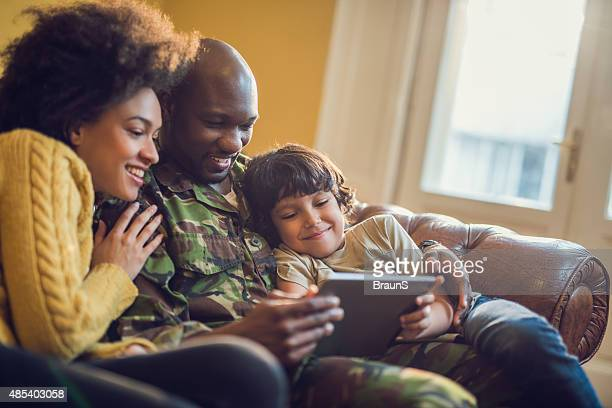 Happy military family relaxing at home and using digital tablet.
