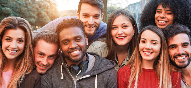 Happy millennial friends from diverse cultures and races having fun posing in front of smartphone camera - Youth and friendship concept - Young multiracial people smiling - Main focus on african man 1176559812