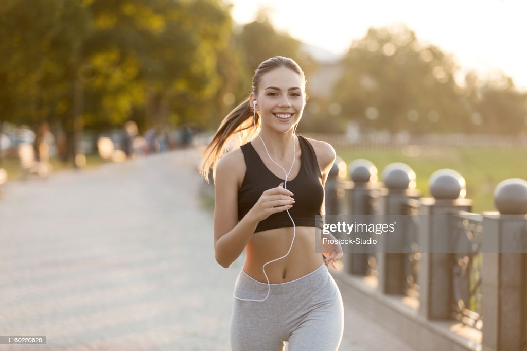 Happy millennial girl running on quay and listening to music : Stock Photo