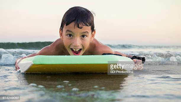 happy mixed race boy uses boogie board in the ocean - galveston stock pictures, royalty-free photos & images