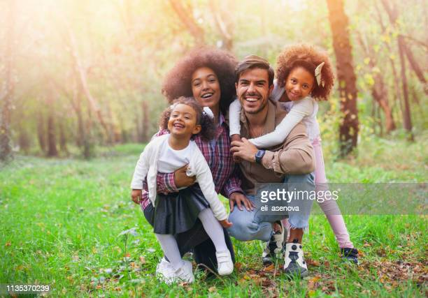 happy mixed race family smiling on the outdoors - mixed race person stock pictures, royalty-free photos & images