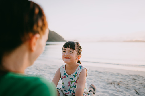 Happy mixed race preschool girl on mother's lap on beach at sunset, Okinawa, Japan - gettyimageskorea
