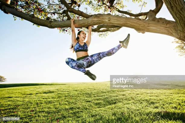 happy mixed race woman hanging on tree branch - schoppen lichaamsbeweging stockfoto's en -beelden
